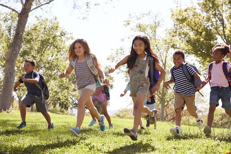 Multi-ethnic group of schoolchildren running in the park Stock Photo