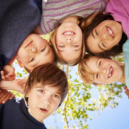 Five schoolchildren standing in a circle and smiling