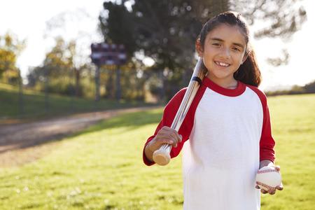 Jeune fille hispanique avec baseball et batte souriant à la caméra Banque d'images - 109004995