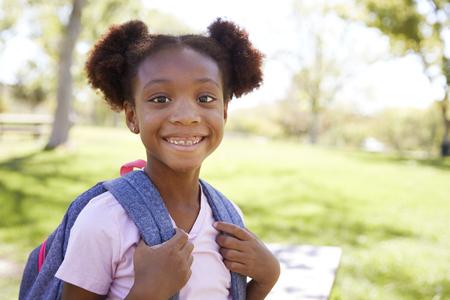 Young black schoolgirl smiling to camera, portrait