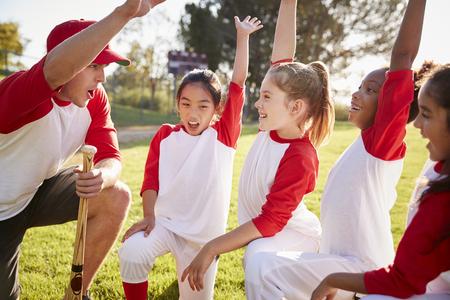 Equipo de béisbol chica arrodillada con su entrenador, levantando las manos Foto de archivo - 109004893