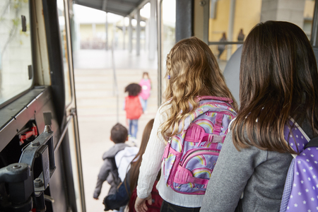 Two girls waiting behind their friends to get off school bus Stock Photo