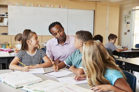 Leraar werkt met basisschoolkinderen aan hun bureau