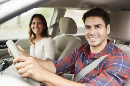 Mixed race young couple driving in car on holiday, portrait Stock Photo