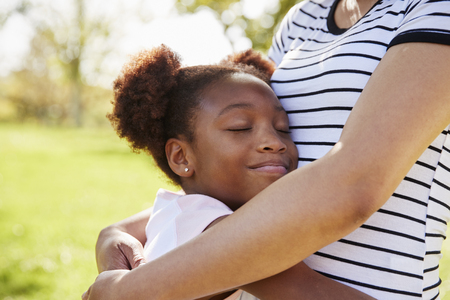 Close Up Of Mother Hugging Daughter In Park Stock Photo
