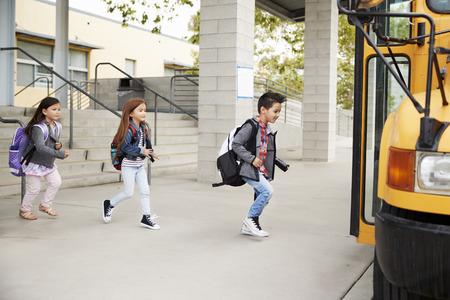 Los niños de la escuela primaria que salen de la escuela para tomar el autobús escolar Foto de archivo