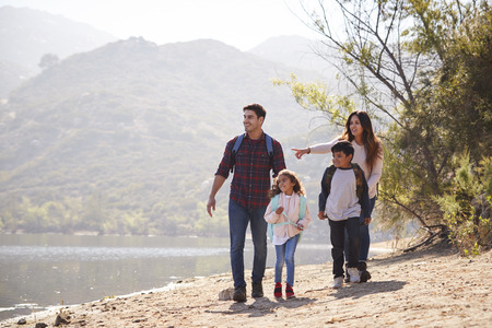 Parents and children hiking together by a lake Stock Photo