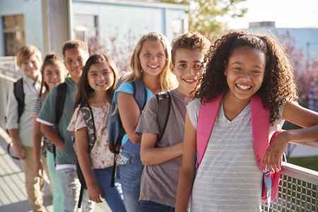 Elementary school kids with backpacks smiling at the camera Stock Photo