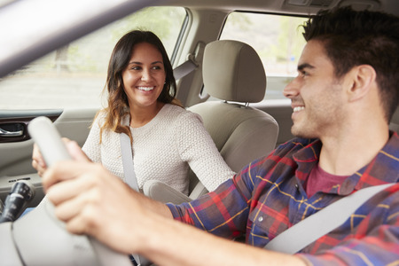 Mixed race young couple smiling in a car on a road trip