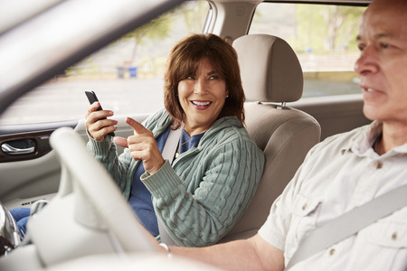 Woman passenger using GPS on smartphone in a car pointing
