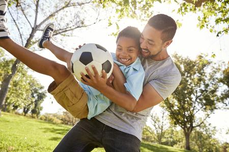 Padre e hijo jugando al fútbol en el parque juntos