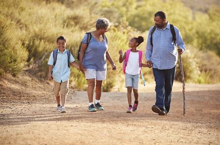 Abuelos con nietos con mochilas de senderismo en el campo juntos