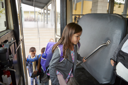 Basisschoolmeisje dat op de schoolbus stapt om naar huis te gaan