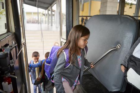 Grundschülerin steigt in den Schulbus, um nach Hause zu gehen