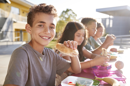 Boy at elementary school lunch table smiling to camera