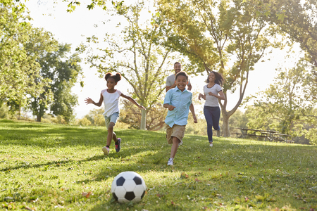 Family Playing Soccer In Park Together 版權商用圖片