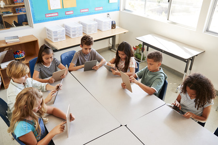 Young kids using tablets in school lesson, elevated view