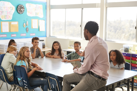 Male teacher with elementary school kids in class discussion