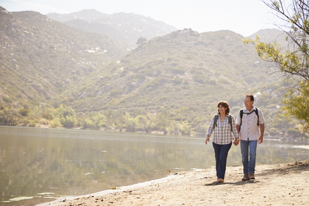 Senior couple hold hands hiking by mountain lake, front view Stockfoto