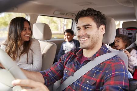 Moeder draait zich om naar haar kinderen op de achterbank van de auto