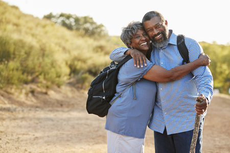 Portrait Of Senior Couple Wearing Backpacks Hiking In Countryside Together