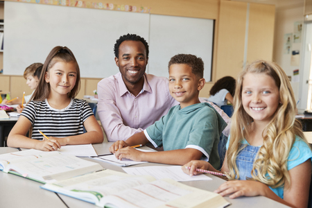 Male school teacher and kids in class smiling to camera