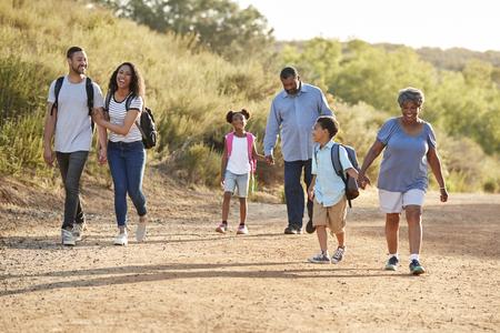 Multi generatie familie rugzakken wandelen op het platteland samen dragen