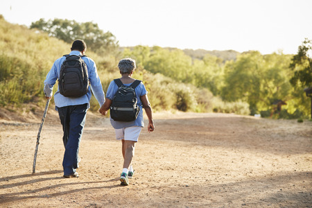 Rear View Of Senior Couple Wearing Backpacks Hiking In Countryside Together Stock Photo