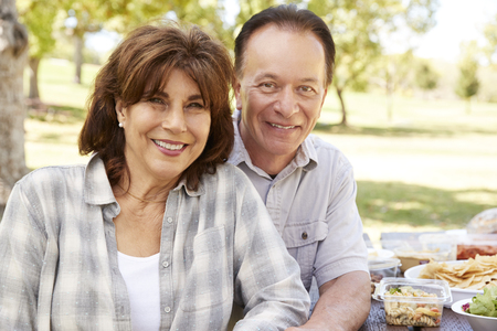 Senior couple sitting at picnic table in a park