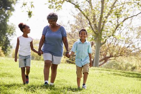 Grandmother Walking In Park And Holding Hands With Grandchildren Stock fotó