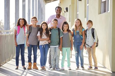 Elementary school teacher and his pupils in school corridor