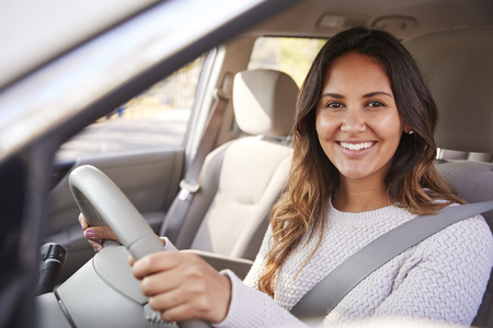 Young woman in car driving seat looking to camera, portrait