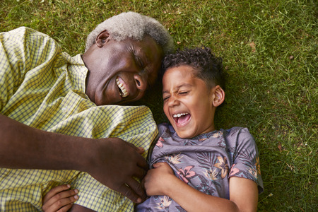 Laughing boy and granddad lying on grass, overhead close up Standard-Bild - 109537990