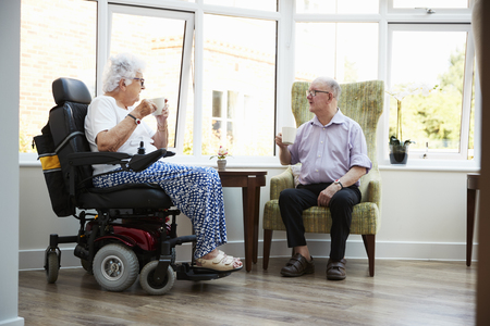 Male And Female Residents Sitting In Chairs and Talking In Retirement Home