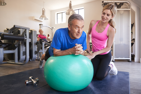 Senior Man Exercising On Swiss Ball Being Encouraged By Personal Trainer In Gym