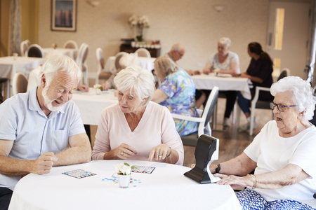 Group Of Seniors Playing Game Of Bingo In Retirement Home Stockfoto