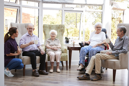 Male And Female Residents Sitting In Chairs And Talking With Carer In Lounge Of Retirement Home Stock Photo