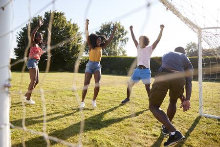 Three adults celebrate scoring goal against their friend Stockfoto