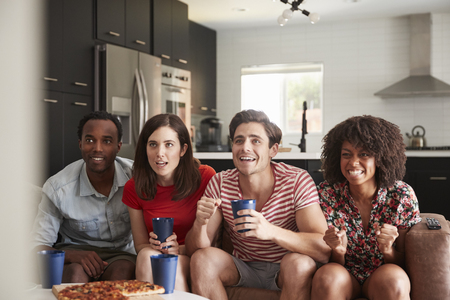 Four young adult friends watching sports on TV at home Banque d'images - 109542987