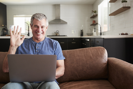 Senior man video calling on laptop at home, waving to screen Stock Photo
