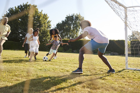 Multi generation black family playing football in a garden