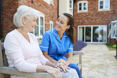 Senior Woman Sitting On Bench And Talking With Nurse In Retirement Home Stockfoto