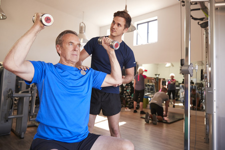 Senior Man Exercising With Weights Being Encouraged By Personal Trainer In Gym