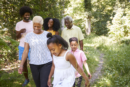 Black girl walks with grandma and family in forest, close up