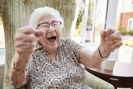 Portrait Of Excited Senior Woman Sitting In Chair In Lounge Of Retirement Home Reklamní fotografie
