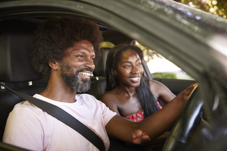 Two young black adults sitting in a car during road trip