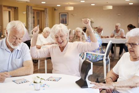 Senior Frau, die das Bingo-Spiel im Altersheim gewinnt