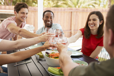 Adult friends sitting at a table outdoors making a toast