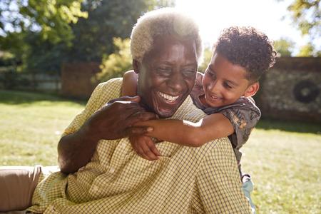 Senior black man sitting on grass, embraced by his grandson 스톡 콘텐츠