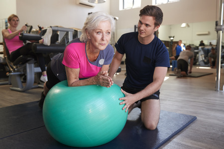 Senior Woman Exercising On Swiss Ball Being Encouraged By Personal Trainer In Gym Stock Photo